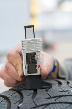 Photo pour La personne avec jauge de profondeur de bande de roulement mesure la profondeur de bande de roulement des pneus - image libre de droit