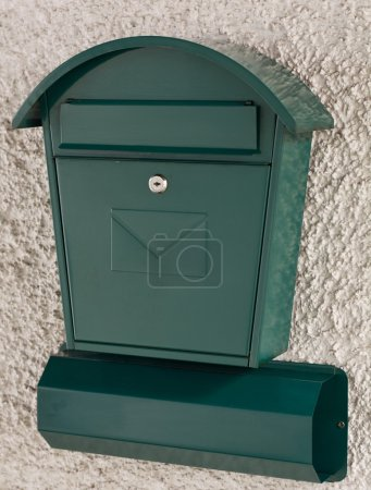 Bright green postbox and newspaper holder...