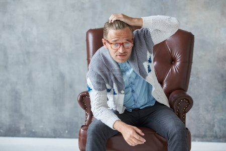 Portrait of a stylish intelligent man with glasses stares into the camera, good view, small unshaven, charismatic, blue shirt, gray sweater, sitting on a brown leather chair, grabs his head