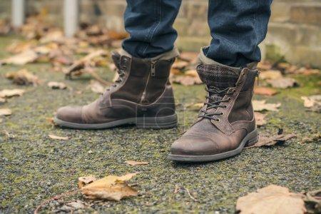 Photo pour Gros plan de bottes en cuir marron contre l'asphalte recouvert de feuilles d'automne - image libre de droit