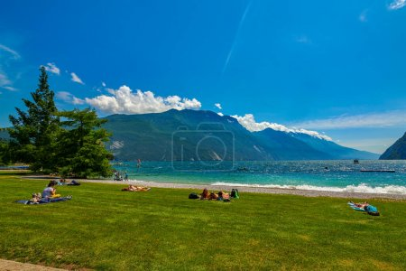 Photo for Riva del Garda,Lago di Garda ,Italy  - 12 June 2020: People who bathe and sit on the beach to tan at Lake Garda, beautiful Lake Garda surrounded by mountains in the summer time - Royalty Free Image