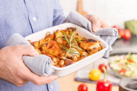 Roasting dish with hot chicken drumsticks in man's hands