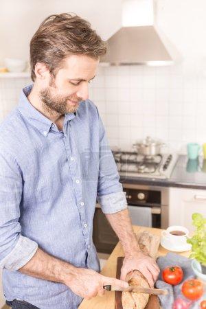 Photo pour Joyeux sourire homme caucasien de quarante ans coupant pain rouleau dans la cuisine lumineuse. Préparation du petit déjeuner . - image libre de droit