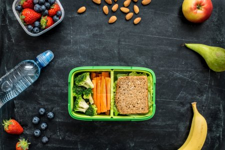 Photo for School lunch box with sandwich, vegetables, water, almonds and fruits on black chalkboard. Healthy eating habits concept - background layout with free text space. Flat lay composition (top view). - Royalty Free Image