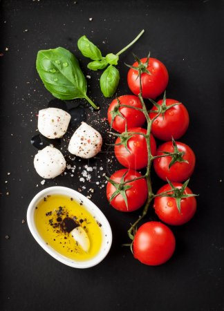 Photo for Cherry tomatoes, mozzarella cheese, basil and olive oil on black chalkboard from above. Italian caprese salad recipe ingredients. - Royalty Free Image