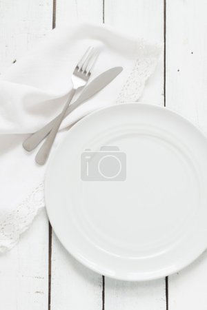 Photo pour White table setting from above. Empty plate, cutlery, napkin on white planked wood table. - image libre de droit