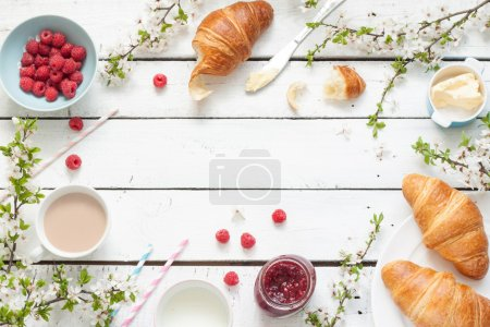 Photo for Romantic french or rural breakfast - cocoa, milk, croissants, jam, butter and raspberries on rustic white wood table from above. Countryside weekend morning concept. Background with free text space. - Royalty Free Image