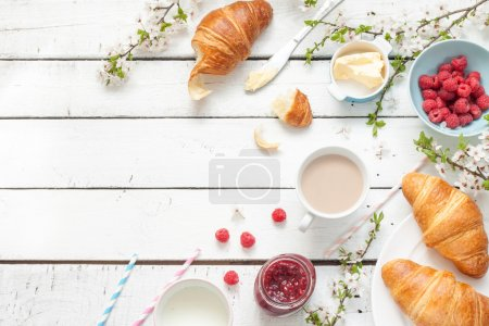 Photo for Romantic french or rural breakfast - cocoa, milk, croissants, jam, butter and raspberries on rustic white wooden table from above. Countryside weekend concept. Background layout with free text space. - Royalty Free Image