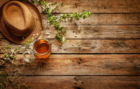 Photo for Country - jar of honey, gardener's hat and blooming tree branch on vintage rustic wood captured from above. Rural background layout with free text space. - Royalty Free Image