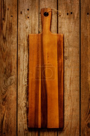 Photo for Empty vintage wooden chopping (cutting) board on rustic planked table captured from above (top view). Rural kitchen scenery. Background layout with free text space. - Royalty Free Image