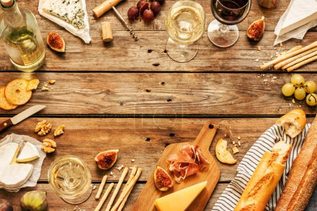 Photo for Different kinds of cheeses, wine, baguettes, fruits and snacks on rustic wooden table from above. Background layout with free text space. - Royalty Free Image