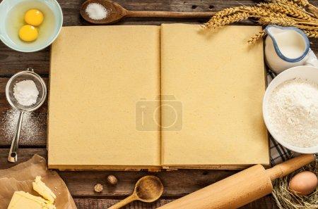 Photo pour Table de cuisine en bois vintage rural avec livre de cuisine vierge, ingrédients de gâteau de cuisson (oeufs, farine, lait, beurre, sucre) et ustensiles de cuisson autour. Fond de pays avec l'espace libre de texte de recette. - image libre de droit