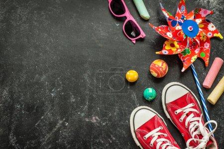 Foto de Juguetes y zapatillas rojas en pizarra negra desde arriba. Infancia - vacaciones o verano concepto divertido. Diseño de fondo con espacio de texto libre. - Imagen libre de derechos