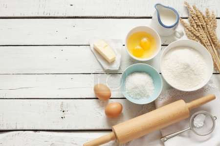 Photo for Baking cake in rustic kitchen - dough recipe ingredients (eggs, flour, milk, butter, sugar) on white planked wooden table from above. Background layout with free text space. - Royalty Free Image