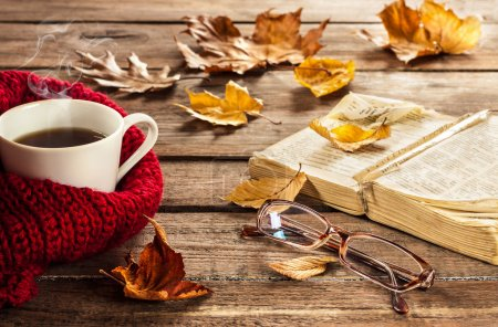 Photo pour Café chaud, livre vintage, verres et feuilles d'automne sur fond bois - concept relax ou retraite - image libre de droit