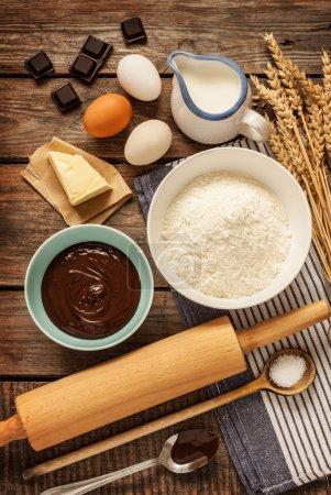 Photo pour Gâteau au chocolat de cuisson dans la cuisine rurale ou rustique. Ingrédients de recette de pâte (oeufs, farine, lait, beurre, sucre) sur la table en bois de cru d'en haut. - image libre de droit