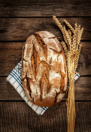Rustic bread and wheat on an old wood table