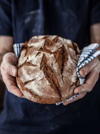 Rustic loaf of bread in man's hands