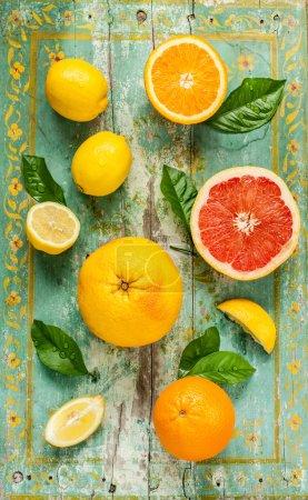 Citrus fruits lemons, grapefruits and oranges on white wood