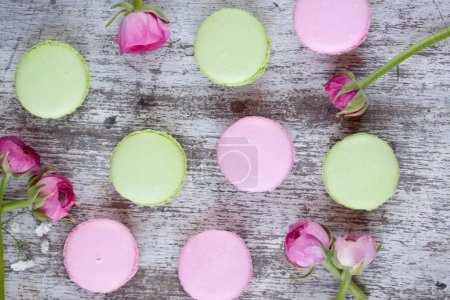 Photo for Colorful macaroons and roses on wooden table - Royalty Free Image