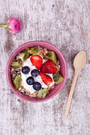 Photo for Muesli with yogurt and fruits on white wooden table - Royalty Free Image