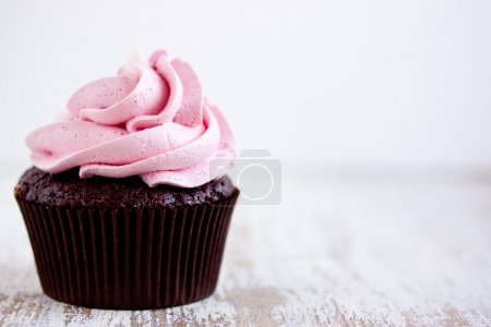 Photo for Pink chocolate cupcake  close up on a wooden table - Royalty Free Image
