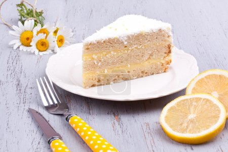Photo for A slice of lemon cake on a wooden background - Royalty Free Image