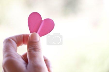 Photo pour Coeur de papier rose main tenue - image libre de droit