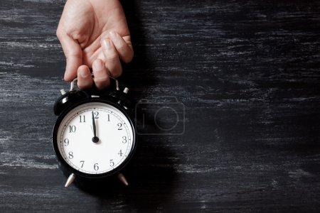 Photo pour Horloge alarn noir sur un fond noir en bois - image libre de droit