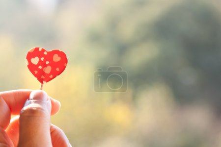 Photo for Holding paper heart on a green background - Royalty Free Image