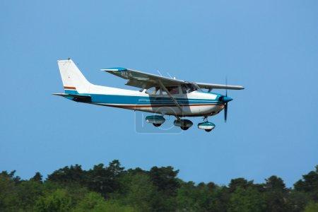 Light general aviation  plane on final over green ...