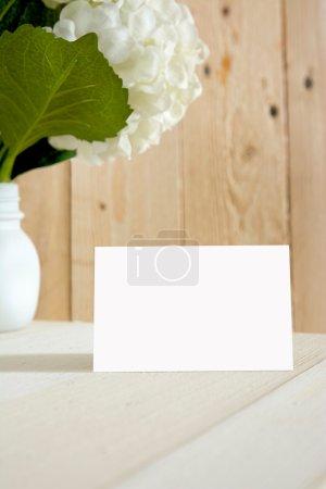 blanck business card, gift box and flowers, sobre fondo a rayas