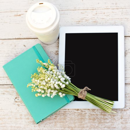 diary, a tablet computerand  lilies of valley