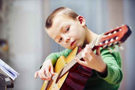 Photo for Little boy is playing the guitar at home - Royalty Free Image