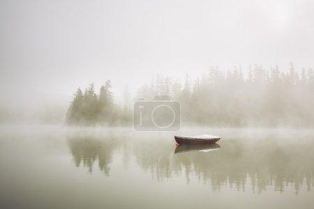 Photo pour Bateau sur le lac au matin brouillard . - image libre de droit