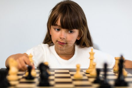 Photo for Young caucasian girl with long hair playing a game of chess. - Royalty Free Image