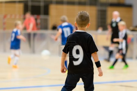 Photo for Young northern european boys playing a indoors soccer training match inside an indoor sports arena. - Royalty Free Image