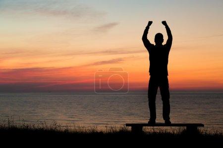 Photo pour Silhouette d'une personne de sexe masculin contre un horizon coloré. - image libre de droit