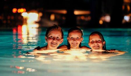 Photo pour Bronzée Caucasiens enfants dans une piscine du resort pendant la nuit. - image libre de droit