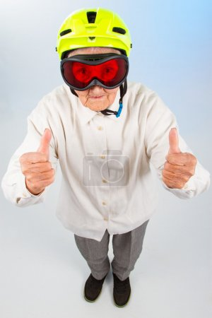 Photo for Funny grandma wearing a yellow bicycle helmet and ski  goggles and showing thumbs up - Royalty Free Image