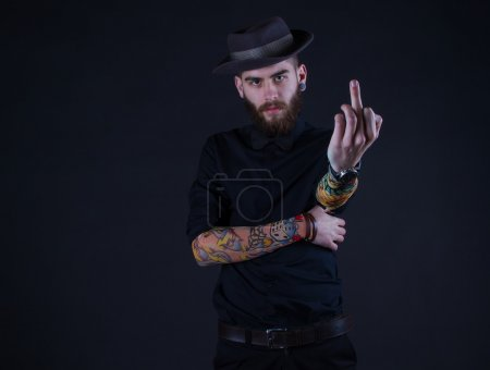 handsome hipster guy showing his middle finger