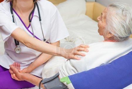 Photo pour Jeune infirmière s'occupant d'une femme âgée aidant ses jours en maison de retraite . - image libre de droit