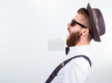 Photo pour Homme jeune hipster portant chapeau, bretelles et noeud-papillon avec la bouche ouverte - image libre de droit