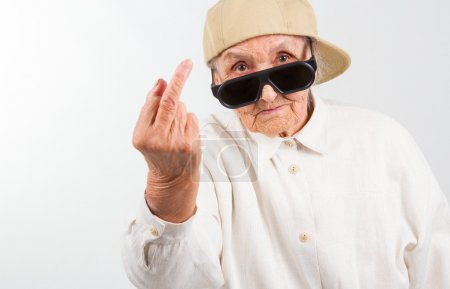 Photo for Funny grandma's studio portrait  wearing eyeglasses and baseball cap, who shows her f-finger ,  isolated on white - Royalty Free Image