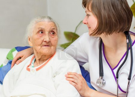 Photo for Happy joyful nurse caring for  an elderly woman  helping her days in nursing home. - Royalty Free Image