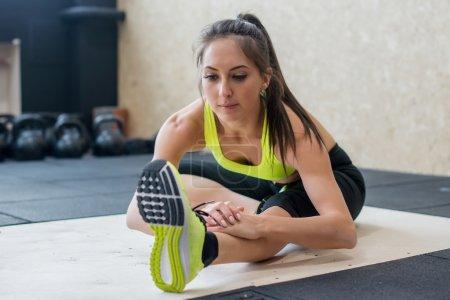 Photo pour Jeune femme étirant hamstring dans la salle de gym, fit femelle faire échauffement sur le tapis . - image libre de droit