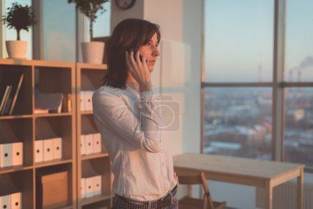 Photo pour Jeune femme parlant à l'aide d'un téléphone portable au bureau le soir. Femme d'affaires concentrée, impatiente, appelant par appareil mobile sur son lieu de travail - image libre de droit