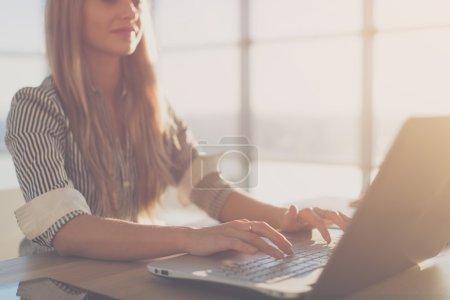 Photo pour Écrivaine, tapant à l'aide de clavier d'ordinateur portable sur son lieu de travail dans la matinée. Femme écrivant des articles en ligne, photo gros plan de vue latérale - image libre de droit