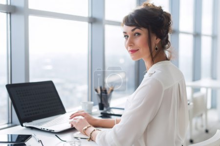 Young female office employee using laptop