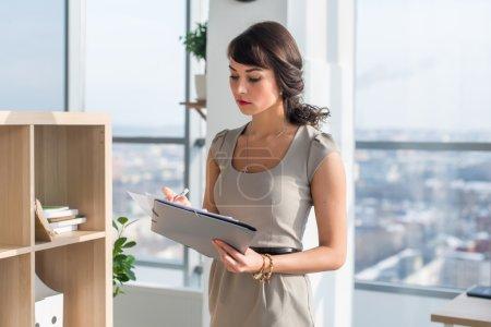 Photo pour Portrait d'une assistante de bureau concentrée, lisant et écrivant de nouvelles idées d'affaires, tenant un dossier papier dans ses mains - image libre de droit